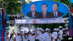 Supporters of Prime Minister Hun Sen's Cambodian People's Party dance under portraits of the party leaders, from left, Chea Sim, Hun Sen and Heng Samrin, during an election campaign in Phnom Penh, Cambodia, Thursday, June 27, 2013. Cambodia's political parties on Thursday kicked off campaigning for the July 28 general election, which is almost certain to see the return to power of Asia's longest-serving leader, Hun Sen.