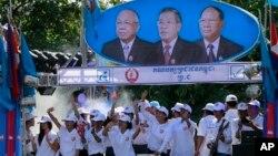Para pendukung partai Rakyat Kamboja berdansa di bawah potret para pemimpin partainya di Phnom Penh, Kamboja (27/6). Dari kiri: Chea Sim, PM Kamboja Hun Sen dan Heng Samrin. Pemerintah Kamboja mencabut larangan siaran program produksi media asing, Sabtu (29/6).