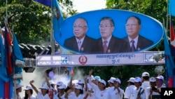 支持柬埔寨人民党的人群在领导人的画像下载歌载舞