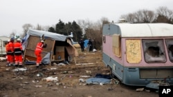 Workers dismantle migrants' dwellings in a makeshift camp near Calais, France, March 1, 2016. The slow tear-down of the encampment in Calais continued Tuesday, angering migrants who live there in squalid conditions in hopes of reaching a better life in Britian.
