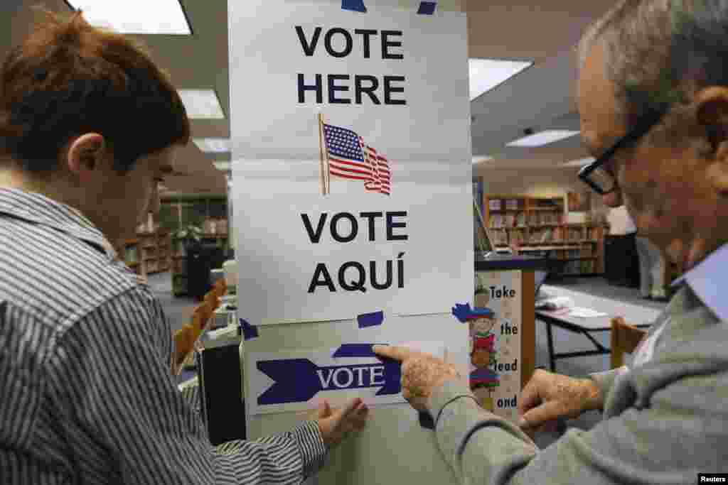 Election workers put up a sign in the library of Spring Hill Elementary School, which is being used as a polling station in McLean, Virginia, Nov. 5, 2013.