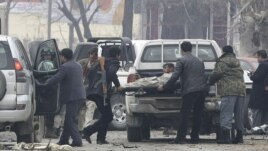 'Yan Afghanistan kennan suna saka wadanda harin kunar bakin wake ya shafa a cikin mota a Kabul, January 16, 2013.