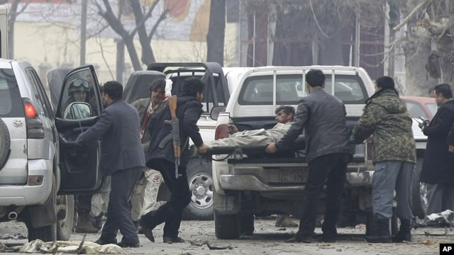 Afghans load a victim, right, into an ambulance at the scene of a suicide car bomb attack in Kabul, Afghanistan, January 16, 2013.