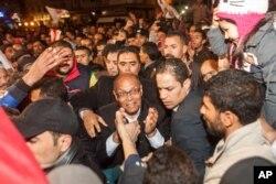 ຜູ້ສະມັກເປັນປະທານາທິບໍດີ ຕູນີເຊຍ ທ່ານ Moncef Marzouki (ກາງ) ໄປກ່າວຄຳປາໄສ ຫຼັງຈາກຮອບທີສອງ ຂອງການເລືອກຕັ້ງ ປະທານາທິບໍດີ ໃນນະຄອນຫລວງຕູນິສ, ວັນທີ 21 ທັນວາ 2014.