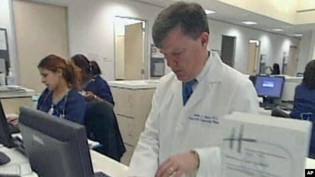 A doctor accesses personalized healthcare information for patients on a computer, February 2011