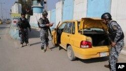 1月23日﹐伊拉克警察在巴格達的檢查站截查車輛。