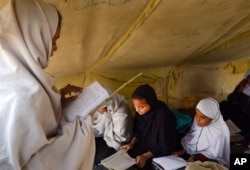 FILE - Afghan students attend class in a tent in Jalalabad, capital of Nangarhar province, Afghanistan, Dec. 16, 2015. Analysts say that by targeting students and education centers, militants are aiming at the heart of the society.