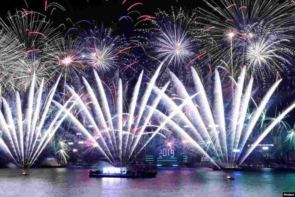 Fireworks explode over Victoria Harbour and Hong Kong Convention and Exhibition Centre during a pyrotechnic show to celebrate the New Year in Hong Kong, China.