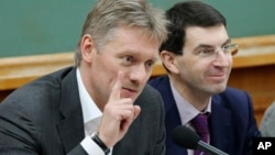 FILE - Kremlin spokesman Dmitry Peskov (L) is seen speaking during a meeting in Moscow, Russia.