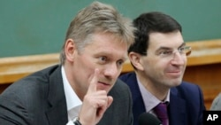 Russian President Vladimir Putin's spokesman Dmitry Peskov, left, speaks during a meeting in Moscow, Russia, Dec. 9, 2012.