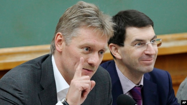 FILE - Russian President Vladimir Putin's spokesman Dmitry Peskov, left, speaks during a meeting in Moscow.