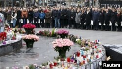 People attend a ceremony at Place de la Republique to pay tribute to the victims of last year's shooting at the French satirical newspaper Charlie Hebdo, in Paris, Jan. 10, 2016.
