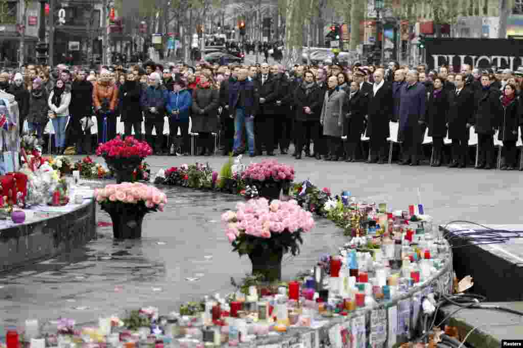 People attend a ceremony at Place de la Republique square in Paris, to pay tribute to the victims of last year's shooting at the French satirical newspaper Charlie Hebdo.
