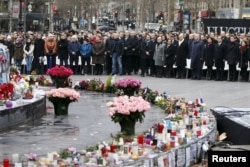 FILE - People attend a ceremony at Place de la Republique square to pay tribute to the victims of the shooting at the French satirical newspaper Charlie Hebdo, in Paris, France, Jan. 10, 2016. Francois Hollande, president at the time of the attack, got a small boost in poopularity for his response to them but ended up finishing his term with record low ratings.