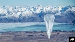 Sebuah balon Google terbang melewati pegunungan Alpen Selatan dengan latar belakang Tekapo, Selandia baru. Balon-balon ini terbang di stratosfer dan memancarkan sinyal Internet ke Bumi. (AP/Jon Shenk)