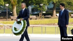 Presiden AS Barack Obama (kiri) didampingi PM Jepang Shinzo Abe saat meletakkan karangan bunga di monumen peringatan Perang Dunia II di Hiroshima, Jepang 27/5 lalu (foto: dok).