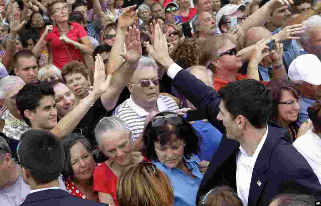 Rep. Paul Ryan high-fives people in the crowd after speaking at a campaign event, Aug. 11, 2012, in Norfolk, Va.