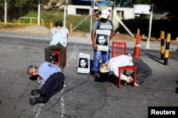 Mannequins depicting torture victims are left by demonstrators protesting against former Salvadoran army General Jose Guillermo Garcia prior to Garcia's arrival, at San Luis Talpa, Jan. 8, 2016. The U.S. deported Garcia after an immigration judge found that he was involved in human rights violations during his tenure as El Salvador's defense minister.