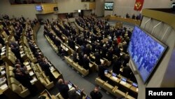 FILE - Russian deputies applaud during voting in the Duma, Russia's lower house of parliament, in Moscow, March 20, 2014.