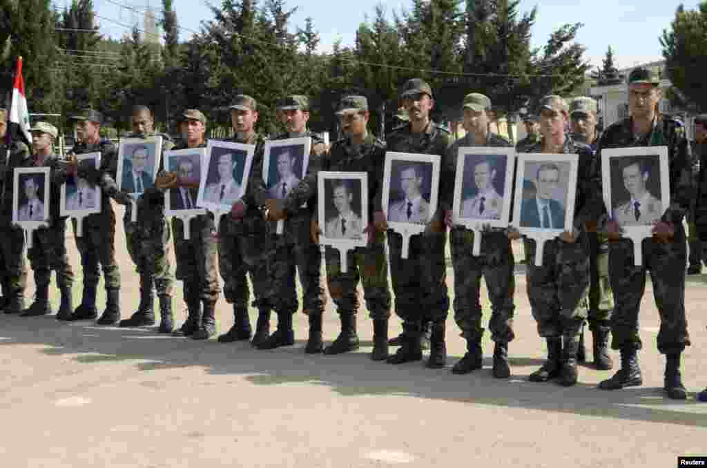 Forces loyal to Syria's President Bashar al-Assad carry pictures of him and his late father, former Syrian president Hafez al-Assad, as they commemorate the 67th anniversary of the founding of the Baath party, at an undisclosed location, April 7, 2014.
