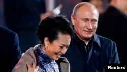 11月10日,正在北京参加APEC会议的俄罗斯总统普京在水立方观看焰火的时候起身为中国第一夫人彭丽媛披上披肩。