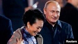 11月10日,正在北京參加APEC會議的俄羅斯總統普京在水立方觀看焰火的時候起身為中國第一夫人彭麗媛披上披肩。