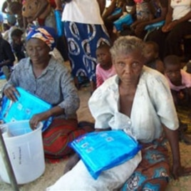 Women receive mosquito nets in Sesheke, Zambia, in September