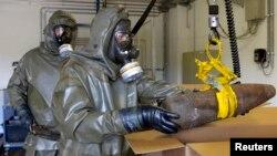 Trabajadores destruyen armas químicas en Siria.