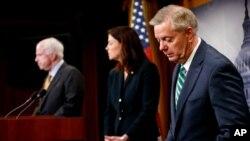 De izquierda a derecha, John McCain, presidente de la Comisión de Servicios Armados del Senado, y los miembros de la comisión senadora Kelly Ayotte y Lindsey Graham.