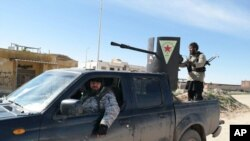 Islamic State militants ride in a Kurdish popular protection unit (YPG) vehicle captured during fighting in Tal Tamr, Hassakeh province, Syria.(AP Photo via militant social media account)