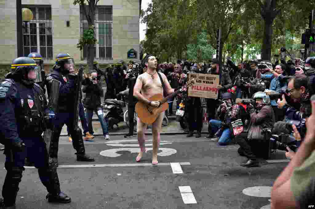A naked man playing guitar stands in front of police officers during a protest called by several French unions against the law reform in Paris.