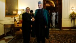 Afghanistan's President Hamid Karzai (R) shakes hands with his Indian counterpart Pranab Mukherjee ahead of their meeting at the Rashtrapati Bhavan presidential palace in New Delhi, May 21, 2013.