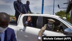 Le président du gouvernement de transition du Mali, le colonel Assimi Goita, salue de son véhicule à son retour d'Accra où il a rencontré les représentants de la CEDEAO le 31 mai 2021.