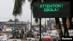 A U.N. convoy of soldiers passes a screen displaying a message on Ebola on a street in Abidjan, Aug. 14, 2014. Sebuah konvoi PBB melewati papan yang memperingatkan masyarakat akan penyebaran Ebola di Abidjan, Pantai Gading.
