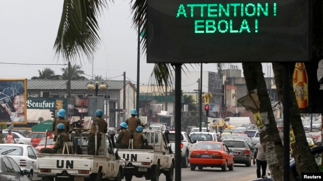 A U.N. convoy of soldiers passes a screen displaying a message on Ebola on a street in Abidjan, Ivory Coast, Aug. 14, 2014.