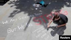 Mladić piše poruku na betonu u centru Manchestera