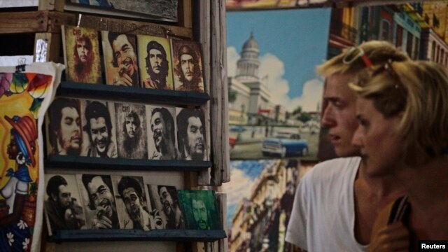Tourists look at portraits of revolutionary leader Che Guevara at an artisans' fair in Havana, Oct. 8, 2013.
