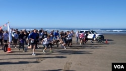 "Runners set off from the beach during the inaugural ""Race the Wave"" 5K fun run/walk. VOA / T. Banse"