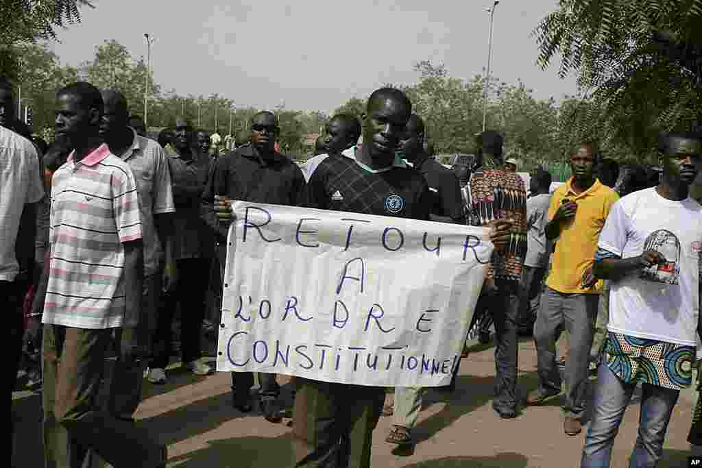 A man carries a sign reading 'Return to constitutional order,' as people gather to protest the recent military coup, in Bamako, Mali, March 26, 2012. (AP)