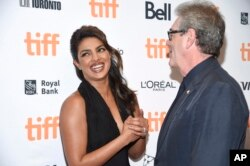 Actress Priyanka Chopra, left, chats with the director and CEO of TIFF Piers Handling at the TIFF Soiree, an annual fundraiser and celebratory kick-off for the 2017 Toronto International Film Festival, at the TIFF Bell Lightbox, Sept. 6, 2017, in Toronto.