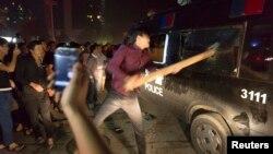 Người biểu tình đập vỡ cửa kính của xe cảnh sát trong cuộc biểu tình ở thành phố Dư Diêu trong tỉnh Triết Giang.