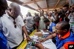 Ghana Incumbent President, John Dramani Mahama candidate of the National Democratic Congress, second left, validates his name before casting his vote during the Presidential and parliamentary election, in Bole Ghana, Dec. 7, 2016.