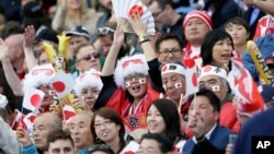 Japan fans celebrate the 34-32 win against South Africa in the Rugby World Cup Pool B match at the Brighton Community Stadium in Brighton, England, Sept. 19, 2015.