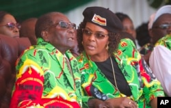 FILE - Zimbabwean President Robert Mugabe and his wife, Grace, follow proceedings during a youth rally in Marondera about 100 kilometers east of Harare, June, 2, 2017.