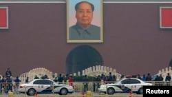 Xe cảnh sát đậu phía trước bức chân dung khổng lồ của Mao Trạch Đông tại lối vào chính của Tử Cấm Thành ở Bắc Kinh.