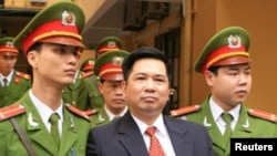 Cu Huy Ha Vu is escorted by policemen after his trial at a court in Hanoi April 4, 2011. Vu, a legal scholar who sued Vietnam's prime minister and called for an end to one-party rule, was sentenced on Monday to seven years in prison.