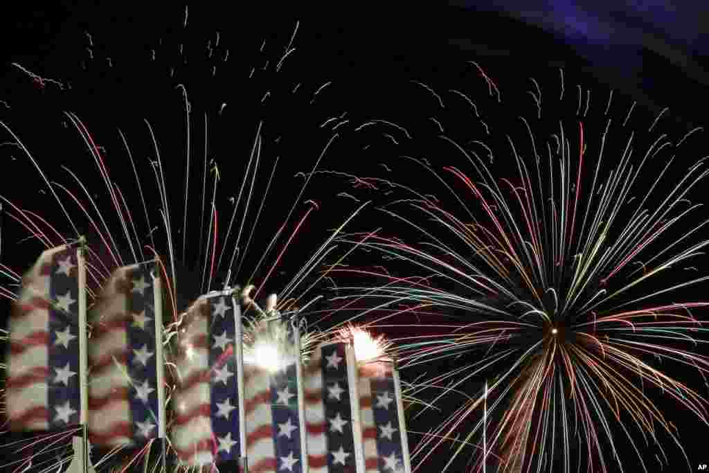Banners with the United States flag colors wave as fireworks burst in the air during the Fourth of July Independence Day show at State Fair Meadowlands, East Rutherford, New Jersey, July 3, 2012.