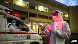 ရန္ကုန္ၿမိဳ႕ရွိ Quarantine Center တခုတြင္ ကိုဗစ္သံသယရွိ လူနာစာရင္းကို စစ္ေဆးေနသည့္ PPE ဝတ္စံုဝတ္ ပရဟိတလုပ္သား တစ္ဦး။ (ေအာက္တုိဘာ ၁၊ ၂၀၂၀)