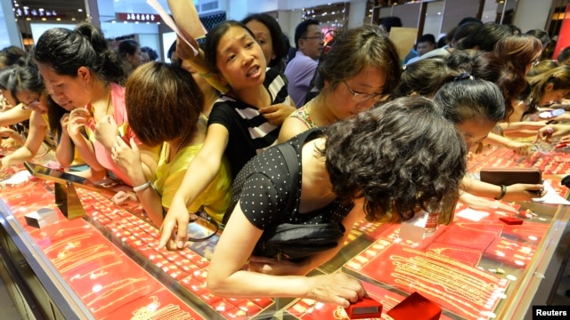 FILE - Customers buy gold accessories at a gold store in Taiyuan, Shanxi province.