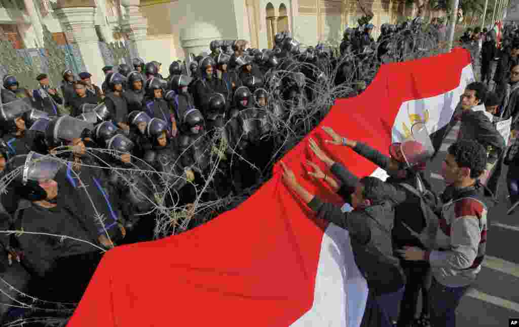 Egyptian protesters hang a giant banner in the colors of Egypt's national flag on barbed wires in front of anti-riot soldiers at the entrance to the presidential palace in Cairo.